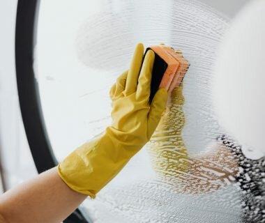 mulher lavando espelho da casa